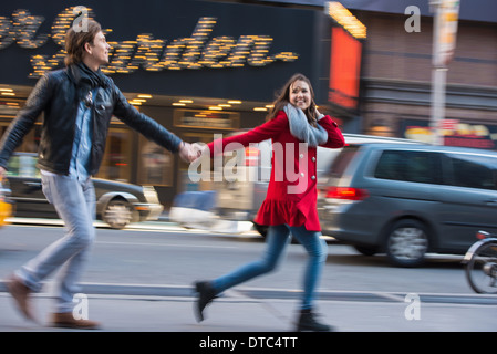 Young couple running along street, New York City, USA - Stock Photo