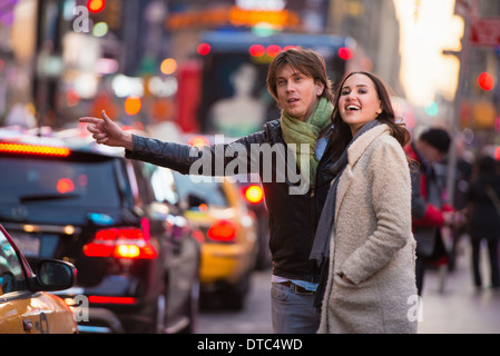 Young tourist couple hailing a cab, New York City, USA - Stock Photo