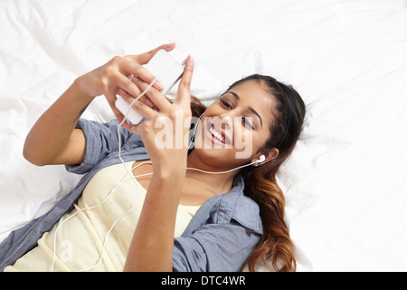 Young woman listening to music in bedroom - Stock Photo
