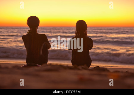 Two girls sitting on beach at sunset looking out to sea - Stock Photo