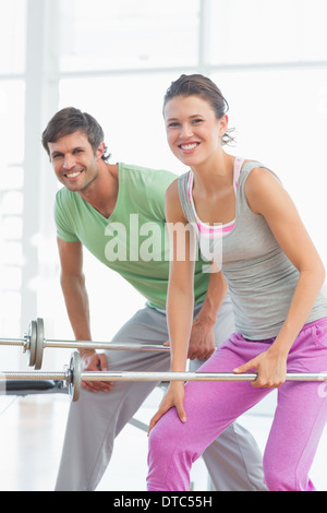 Fit young man and woman lifting barbells - Stock Photo