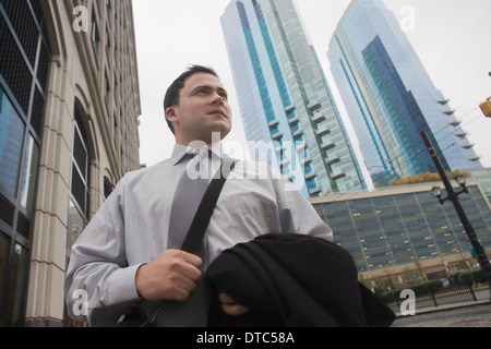 Businessman in city surrounded by skyscrapers - Stock Photo