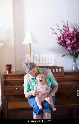 Grandmother and granddaughter sitting on bench - Stock Photo