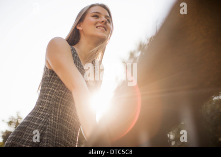 Teenage girl leaning on railings in park - Stock Photo