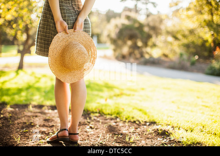 Cropped image of teenage girl holding sunhat behind her back - Stock Photo