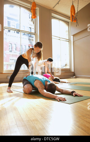 Yoga teachers assisting people in class - Stock Photo