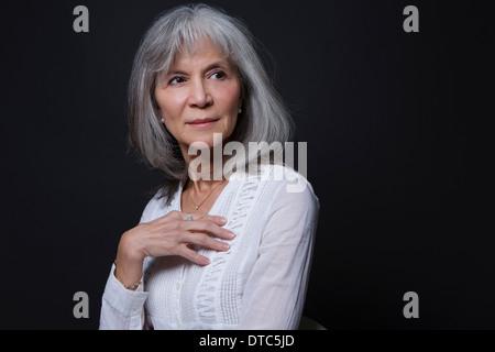 Studio portrait of confident senior woman - Stock Photo
