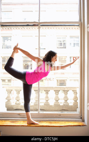 Woman doing dancer pose by window - Stock Photo