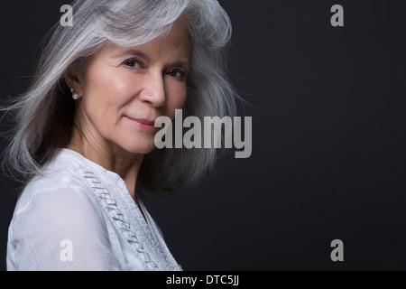 Studio portrait of beautiful senior woman - Stock Photo