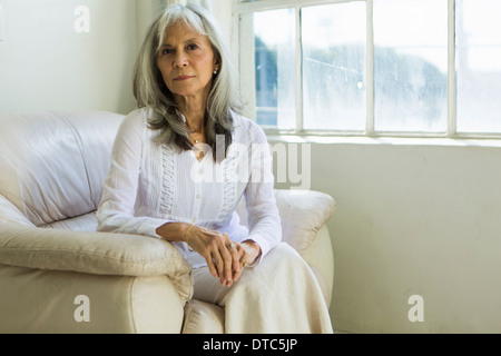 Portrait of senior woman sitting in apartment - Stock Photo