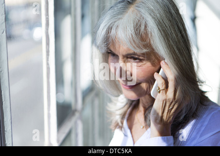Senior woman using smartphone whilst looking out of window - Stock Photo