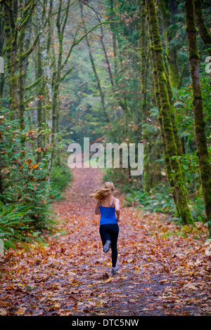 Girl jogging in forest - Stock Photo