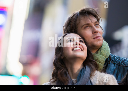 Young couple on vacation looking up, New York City, USA - Stock Photo