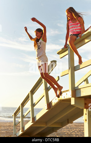 Two girls playing at beach, jumping off boardwalk - Stock Photo