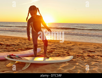 Young girl at beach wearing wetsuit and standing on surfboard - Stock Photo