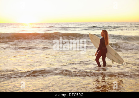 Girl carrying surfboard in sea wearing wetsuit - Stock Photo