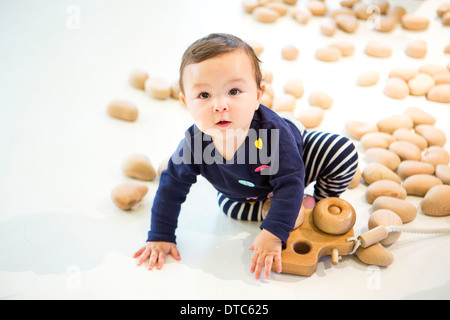 Baby girl sitting on floor with toy - Stock Photo