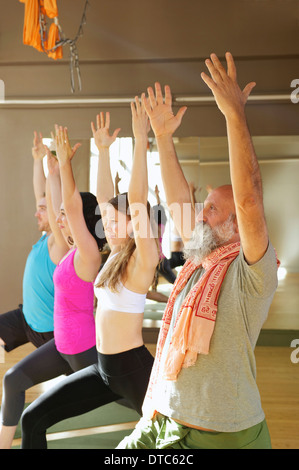 People in warrior pose in yoga class - Stock Photo