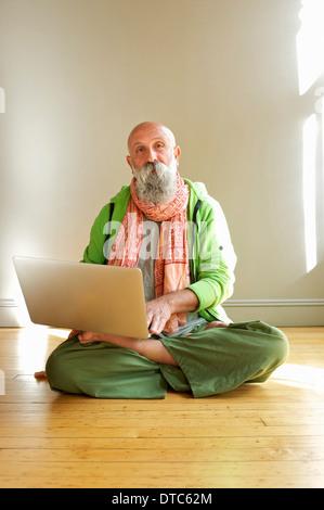 Senior man using laptop in lotus position - Stock Photo