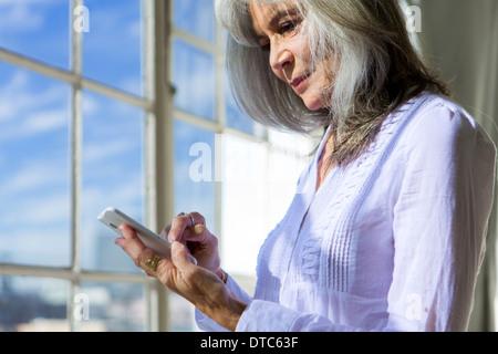 Senior woman using touchscreen on smartphone - Stock Photo