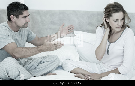 Conflicting couple in bed - Stock Photo