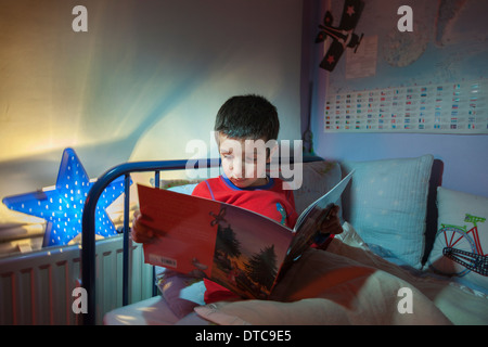 Young boy,reading a bedtime story in his bed - Stock Photo