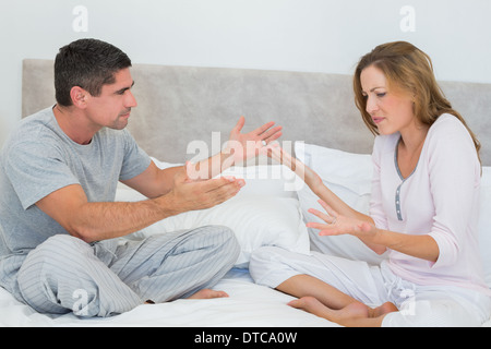 Frustrated couple in bedroom - Stock Photo