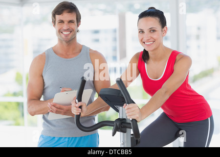 Woman with instructor working out at spinning class in bright gym - Stock Photo