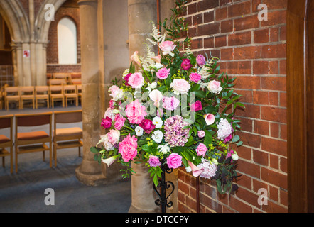Flower arrangement as a self-standing floral display mainly of pink and red roses at Christ Church, Woking, Surrey, - Stock Photo