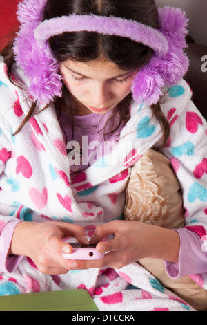 Teenage girl chatting online on her mobile phone - Stock Photo