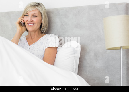 Smiling woman using mobile phone in bed - Stock Photo