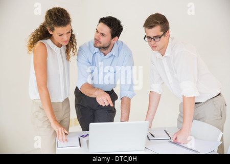 Business people discussing over laptop - Stock Photo