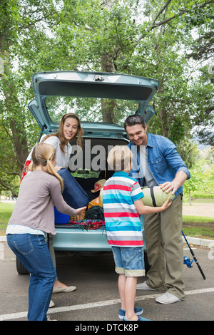 Family unloading car trunk while on picnic - Stock Photo
