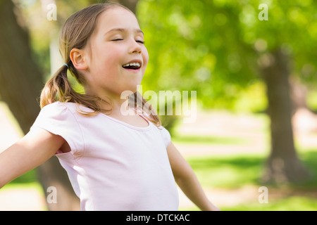 Girl with arms outstretched and eyes closed at park - Stock Photo