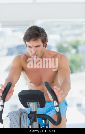 Determined man working out at spinning class in bright gym - Stock Photo