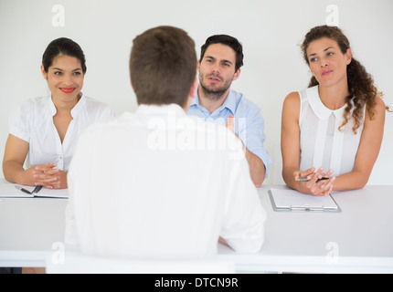 Man being interviewed by business people - Stock Photo