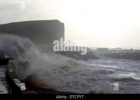 West Bay, Dorset, UK, 15 February 2014: Huge waves crash over West Bay's Jurassic Pier after a night where the wind - Stock Photo