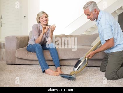 Woman filing nails while man vacuuming area rug - Stock Photo