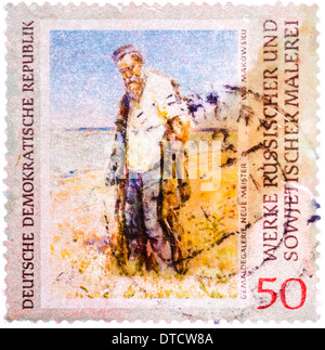 Stamp printed in the Germany (GDR) shows picture by Vladimir Makovsky 'Man on the River' - Stock Photo