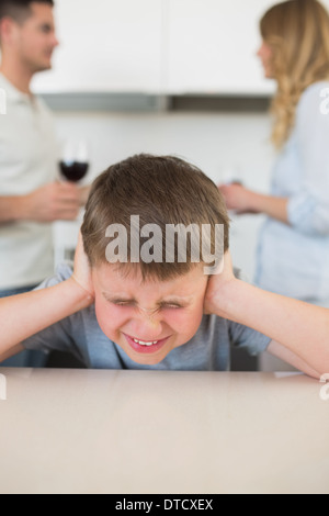 Furstrated boy covering ears while parents arguing - Stock Photo