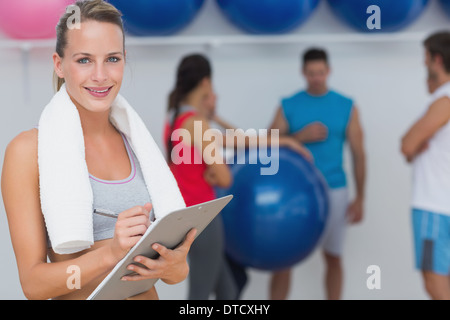 Female trainer holding clipboard with fitness class in background - Stock Photo