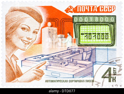 Stamp printed in USSR, shows mail processing (woman postal official) and automatic letter sorting machine, circa - Stock Photo