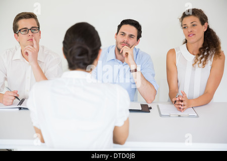 Woman being interviewed by business people - Stock Photo