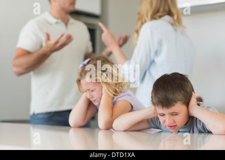 Children covering ears while parents arguing - Stock Photo
