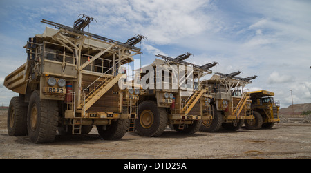 Massive hitatchi and komatsu mining haul trucks parked up in a line in a  open cast copper and gold mine. - Stock Photo