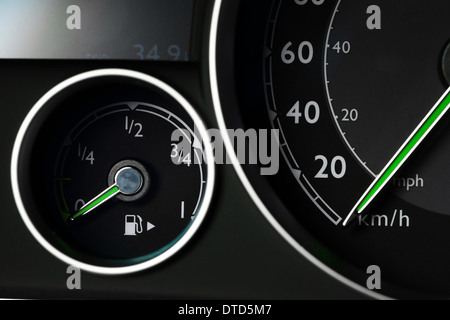 Close-up shot of a fuel gauge and a speedometer in a car