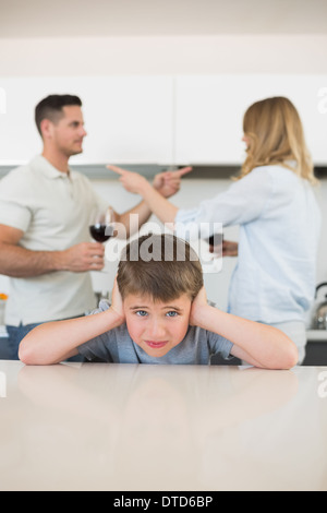 Boy covering ears while parents arguing - Stock Photo