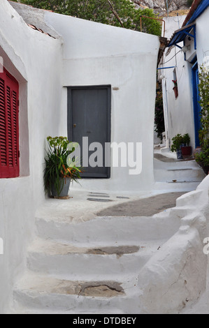 Steps, white painted narrow street and small houses in the traditional Anafiotika neighborhood of Plaka, Athens - Stock Photo