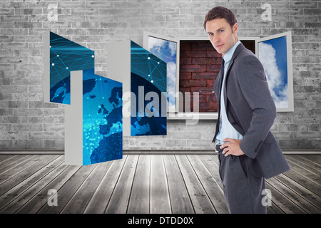 Composite image of serious businessman with hands on hips - Stock Photo