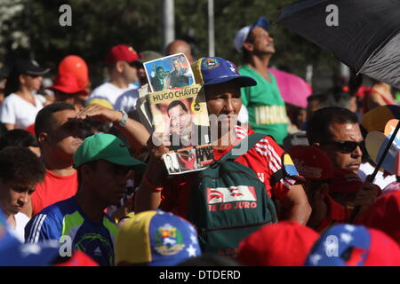 Caracas, Venezuela. 15th Feb, 2014. A demonstrator holds images of late President Hugo Chavez, during the 'March for Peace', called on Friday by Venezuelan President Nicolas Maduro, in the city of Caracas, capital of Venezuela, on Feb. 15, 2014. Credit:  AVN/Xinhua/Alamy Live News